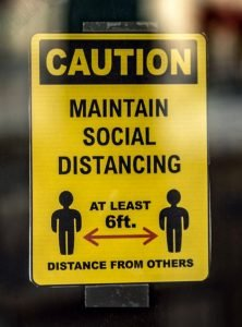 """Storefront sign that reads """"Caution Maintain Social Distancing At Least 6ft. Distance From Others."""""""